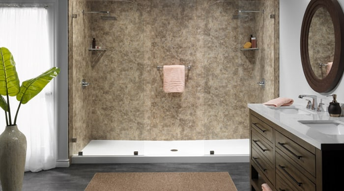 A stylish modern shower with glass doors and granite walls in a well-appointed bathroom. A potted plant is visible to the left. When you choose bathroom remodeling by Molitor, your space will be welcoming and stylish.